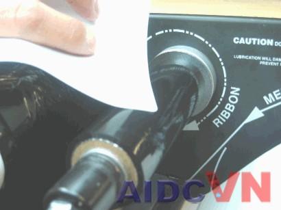 Dùng 1 miếng nhãn để dính vào cuộn mực có trên máy